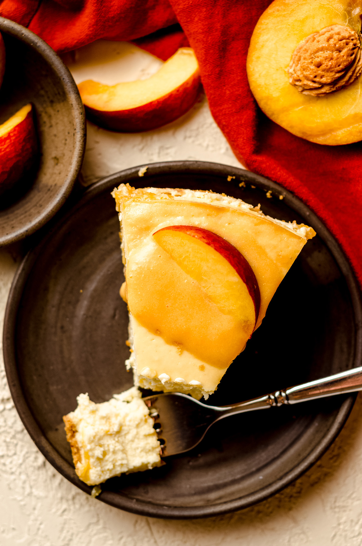 aerial photo of slice of peach cheesecake topped with peach curd and a peach slice on a plate with a fork
