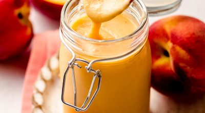 a spoon pulling a scoop of peach curd out of a jar