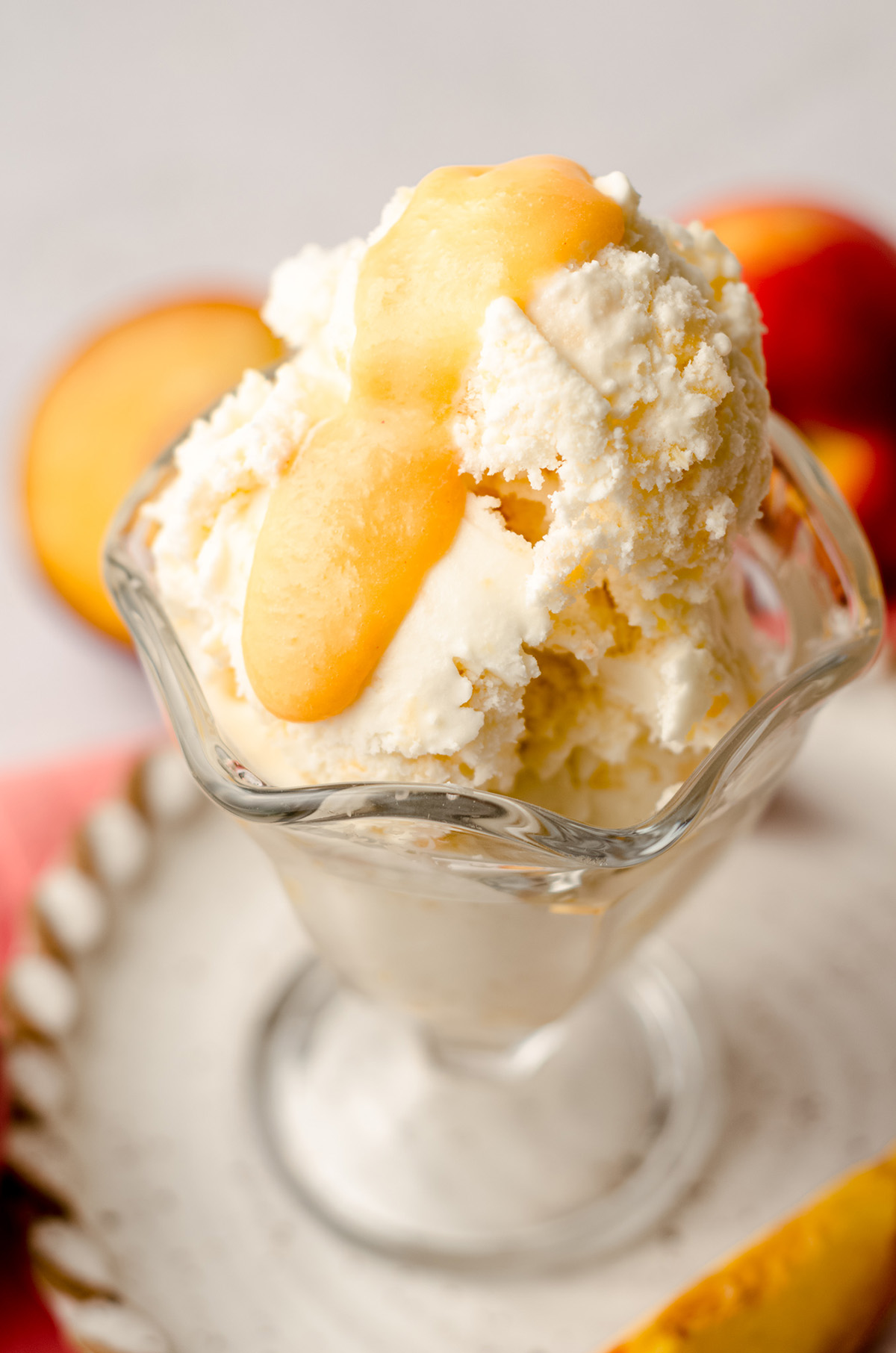 homemade peach ice cream in a glass dish with peach curd on top