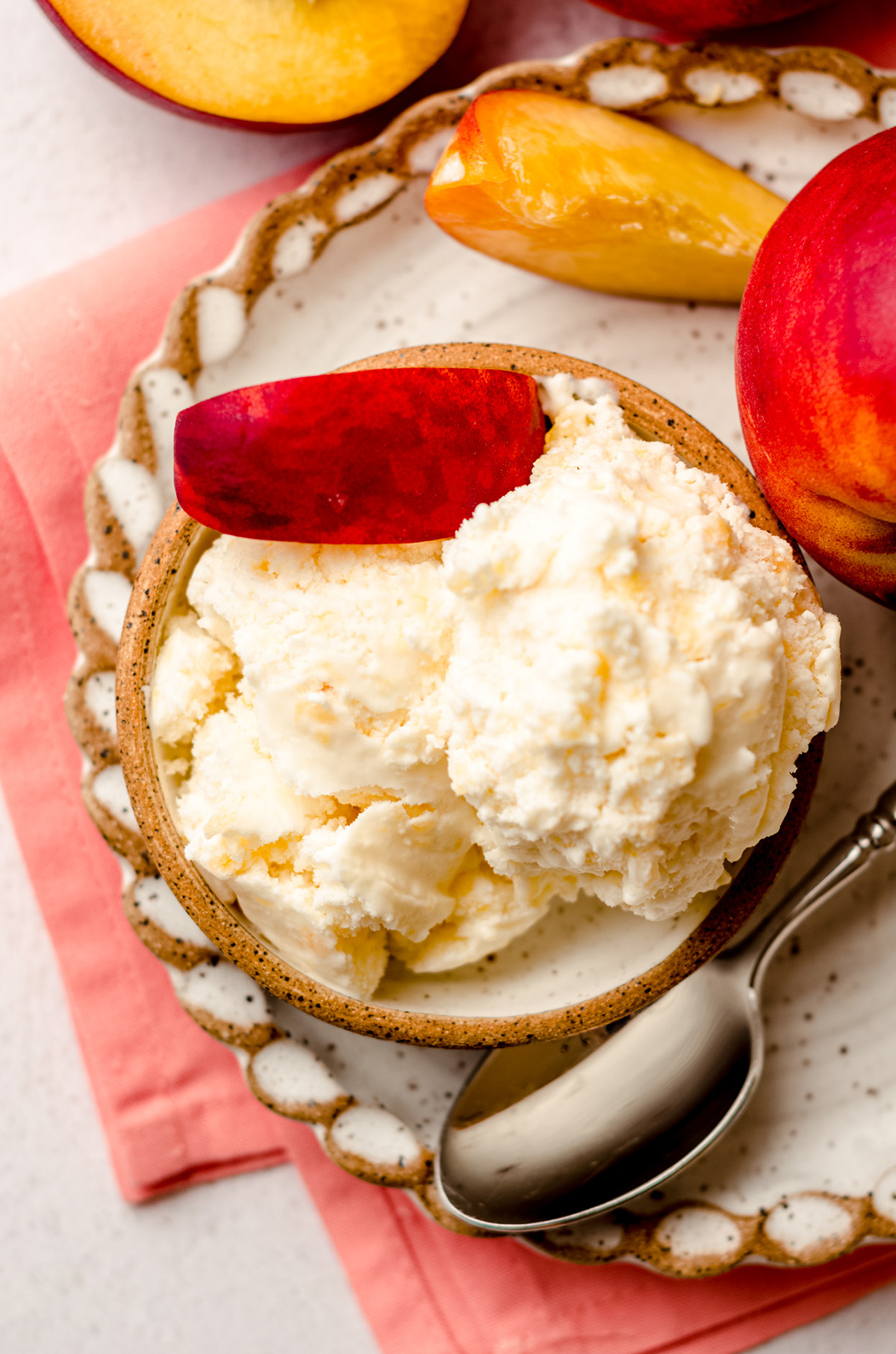 aerial photo of homemade peach ice cream in a bowl with a spoon