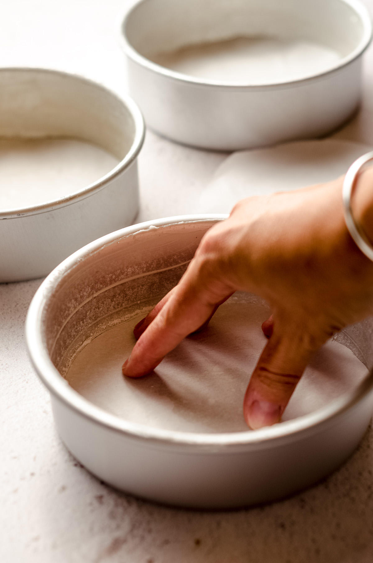 pressing parchment into the bottom of a cake pan