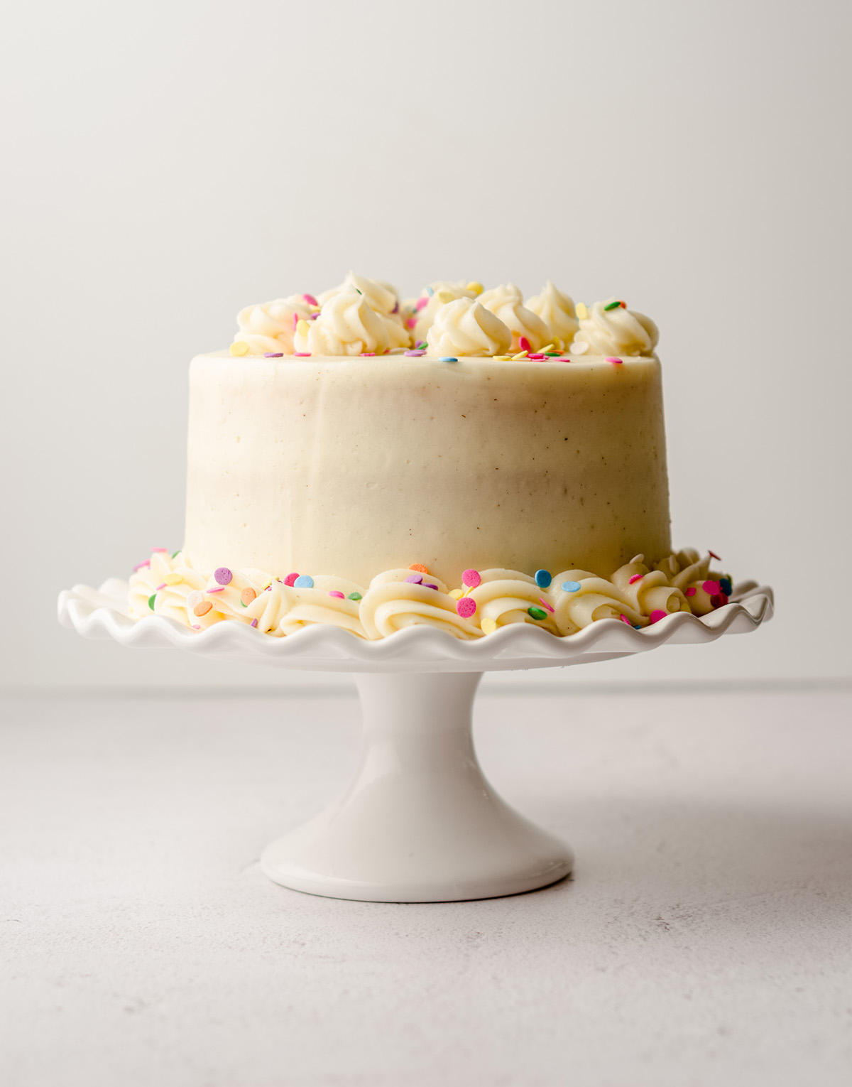 a small vanilla cake with rainbow sprinkles on a white cake stand
