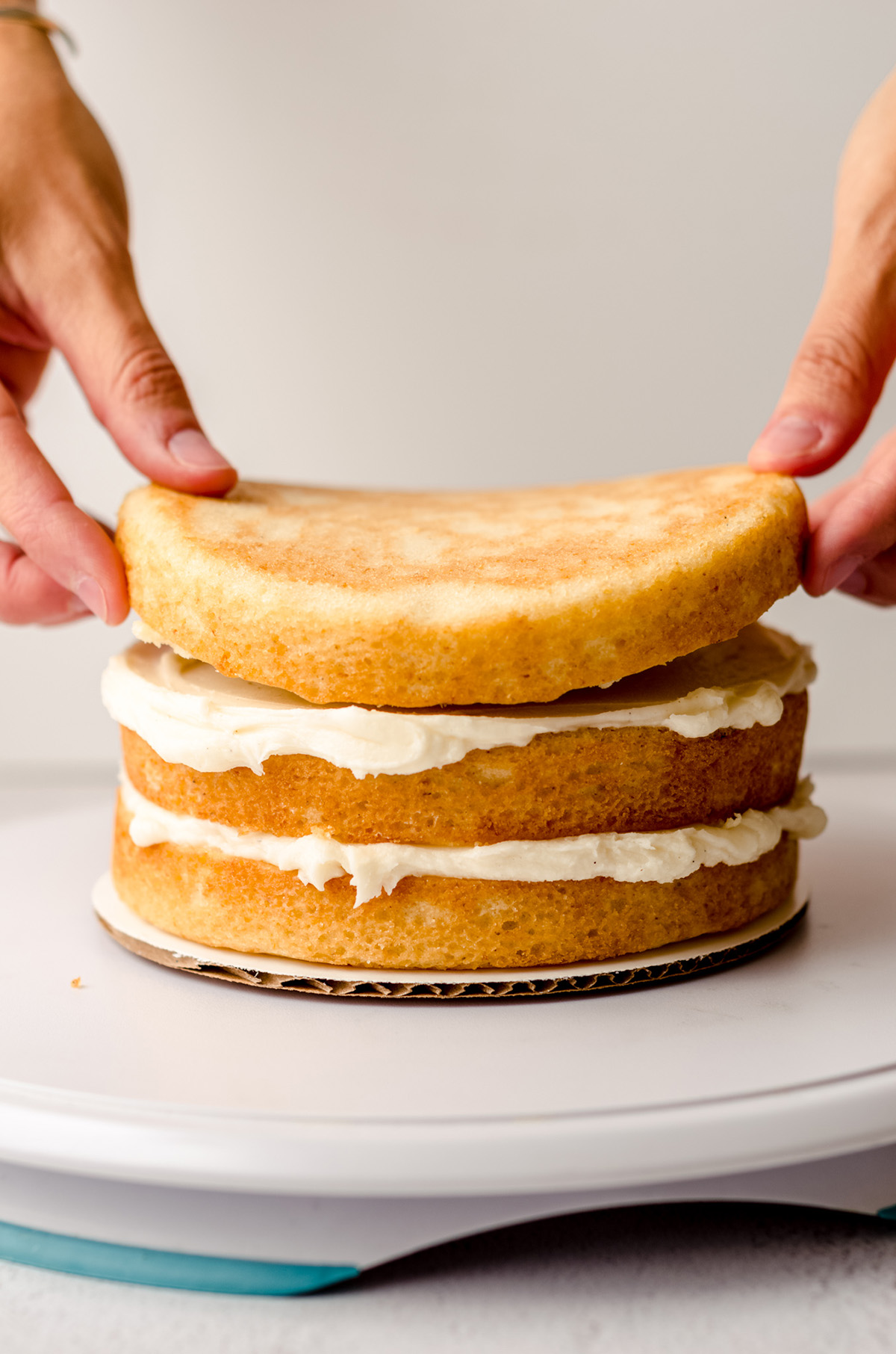 hands putting a third layer on a stacked cake