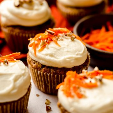 carrot cake cupcakes with cream cheese frosting with shredded carrots and pecans on top