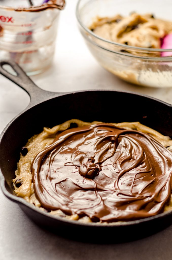 nutella on top of chocolate chip cookie dough in a skillet