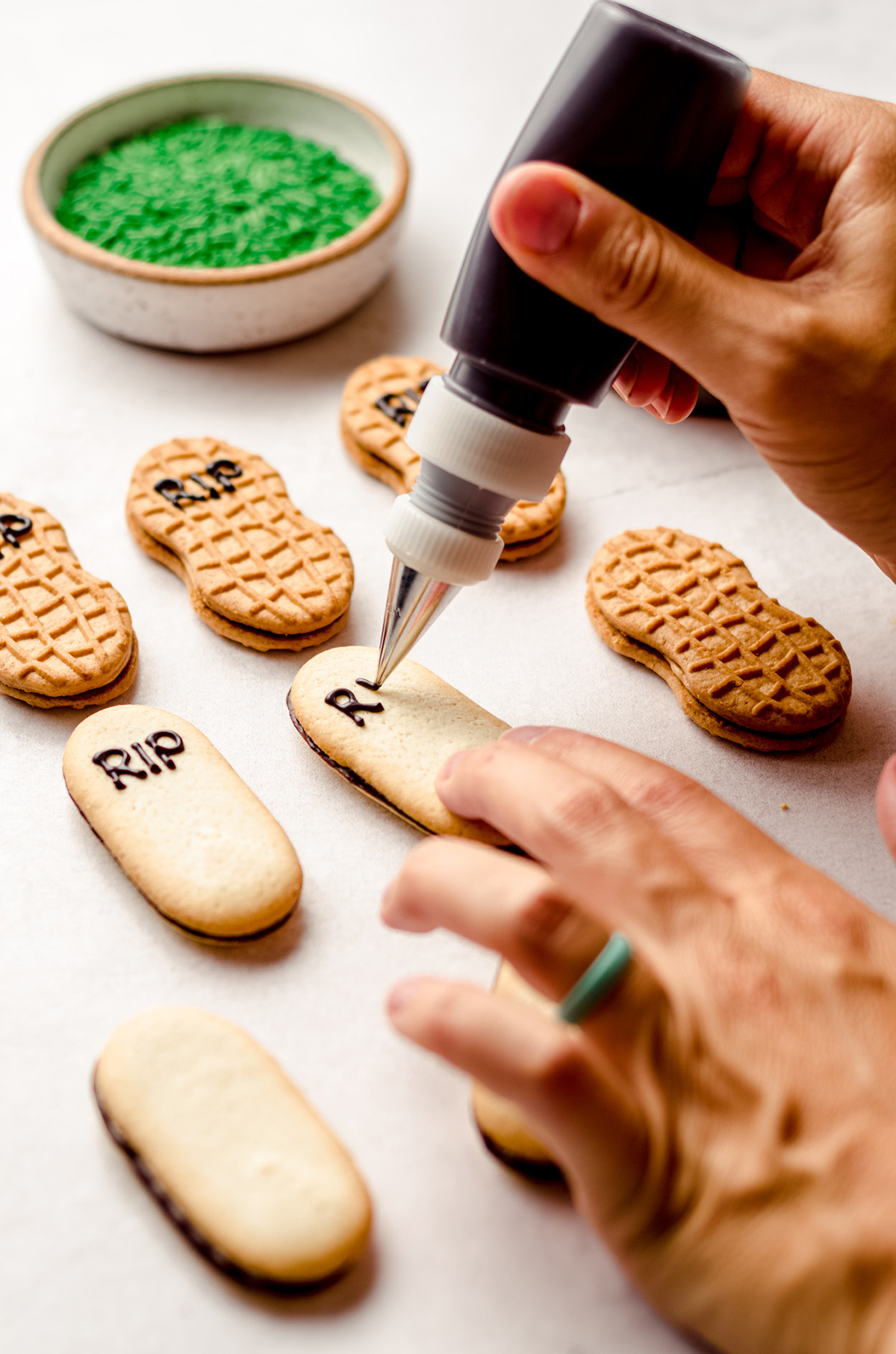 hand piping the letters R.I.P. onto a milano cookie to make a gravestone for graveyard pudding cups