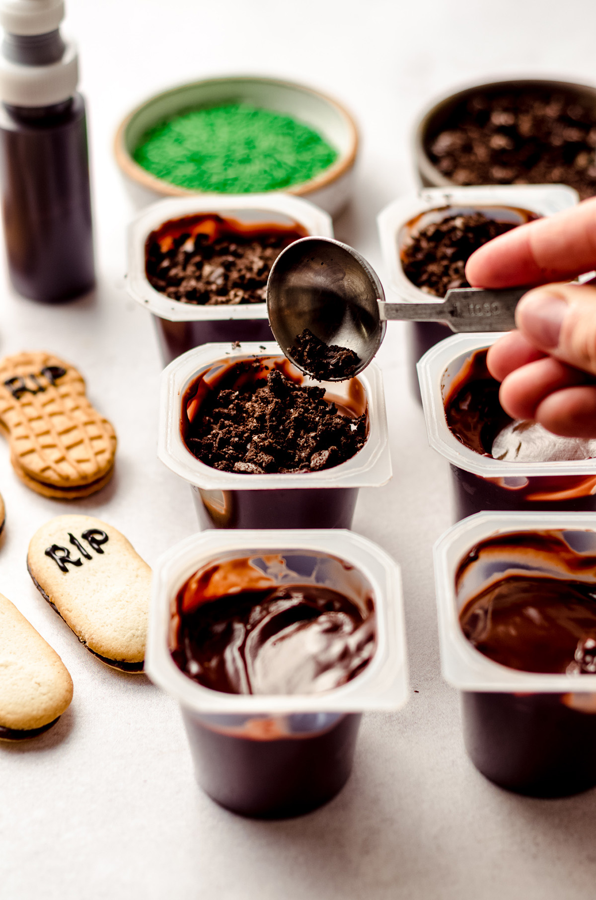 spooning crushed oreos on top of pudding cups to make graveyard dirt