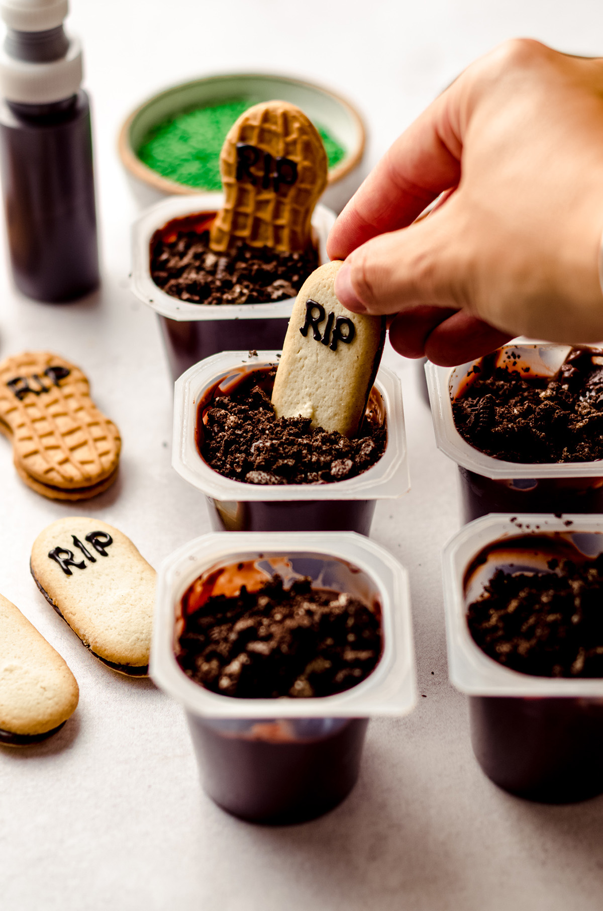 hand placing a milano cookie into a pudding cup to make graveyard pudding cup