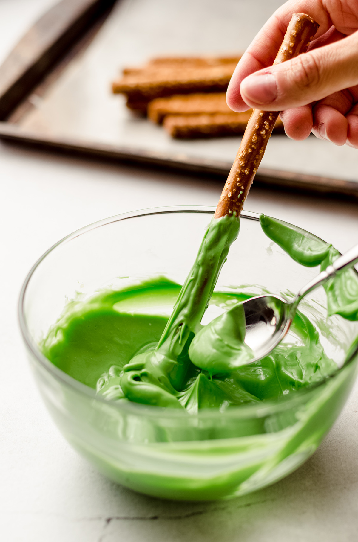 dipping a pretzel rod into green candy coating to make witch finger pretzels