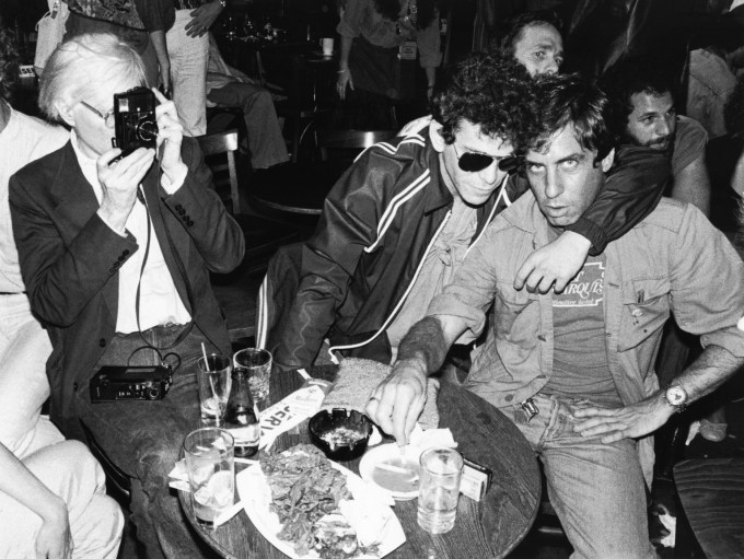A picture a Andy Warhol (left) taking a picture of Danny Fields (right) with Lou Reed (middle).