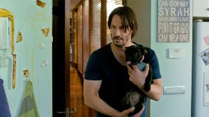 Keanu Reeves (Evan) holding his Frenchie in KNOCK KNOCK. Courtesy of Lionsgate.