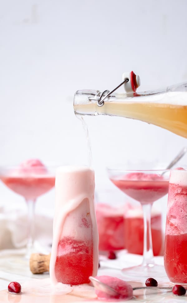 A champagne cocktail fitting for the season Cranberry Apple Mimosa Floats are a way to have your dessert and your after dinner drink in one! Cranberry Dessert Mimosa Cocktail for Fall , Thanksgiving and Christmas   homemade gluten free sorbet mimosa recipe   pink apple cider punch for a crowd   #cranberry #apple #sorbet #champagnecocktail