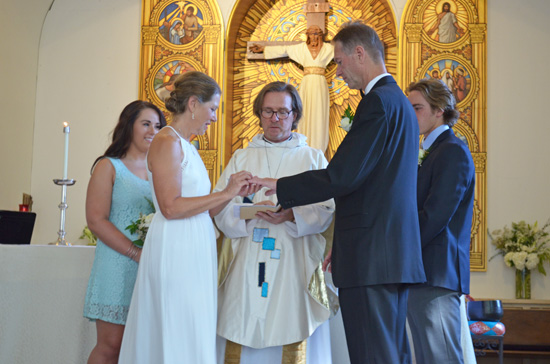 Father Peter Rood of Holy Nativity Episcopal Church blesses the wedding rings.  Photo by Mike Gitchell.