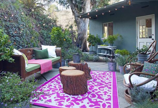 wohnzimmer im garten einrichten mit teppich in lila und wei und runde couchtische aus holz