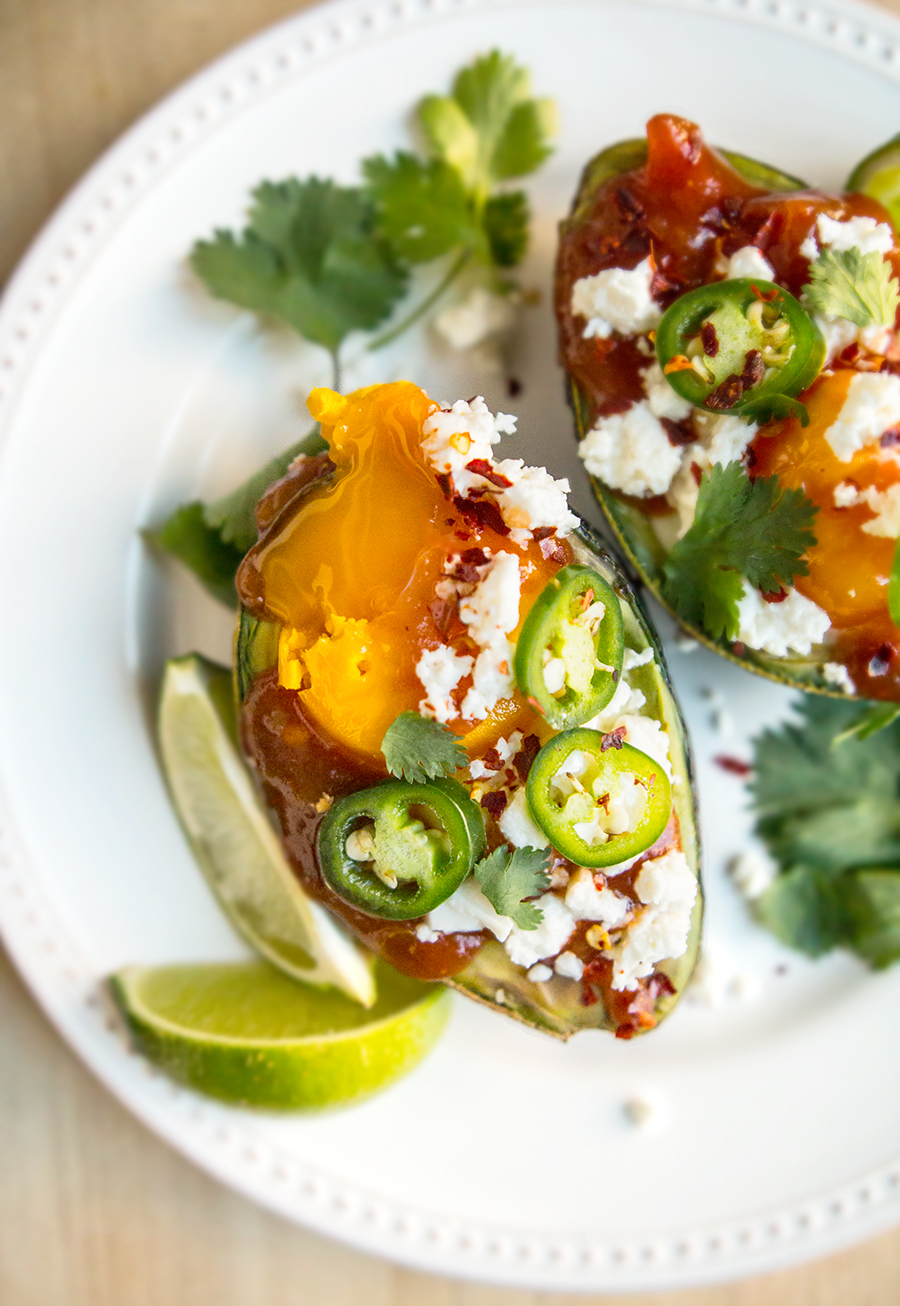 Egg-Stuffed Avocado Olé is eggs baked in an avocado and topped with salsa, queso fresco, cilantro, red chili flakes, jalapeño... even a dash of lime!