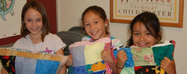 Girls with the patchwork pillows they sewed.