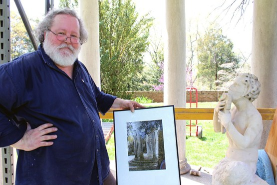 Sculptor Scott McKee of Fredericksburg poses with Pan, the limestone statue he restored and reinstalled at Chatham Manor, and a photograph he used during the months-long restoration project.