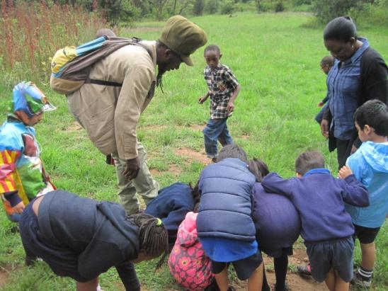 Martin, a guide from Nature Kenya Youth Committee helping the children to spot insects