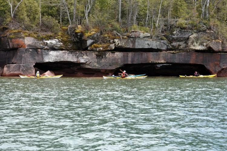 Sea kayakers paddling near shoreline sea caves on Bear Island