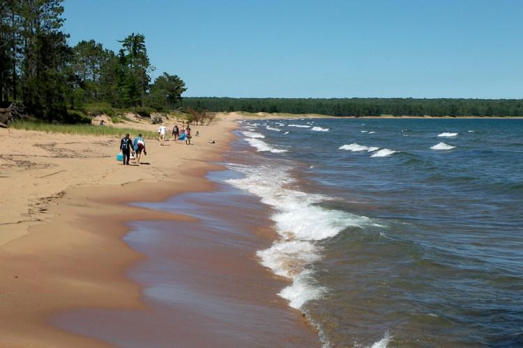 visitors walking on Julian Bay beach