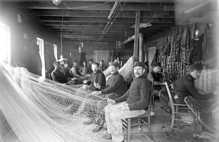 Commercial fishermen mending nets at the Booth Fishery twine shed in Bayfield