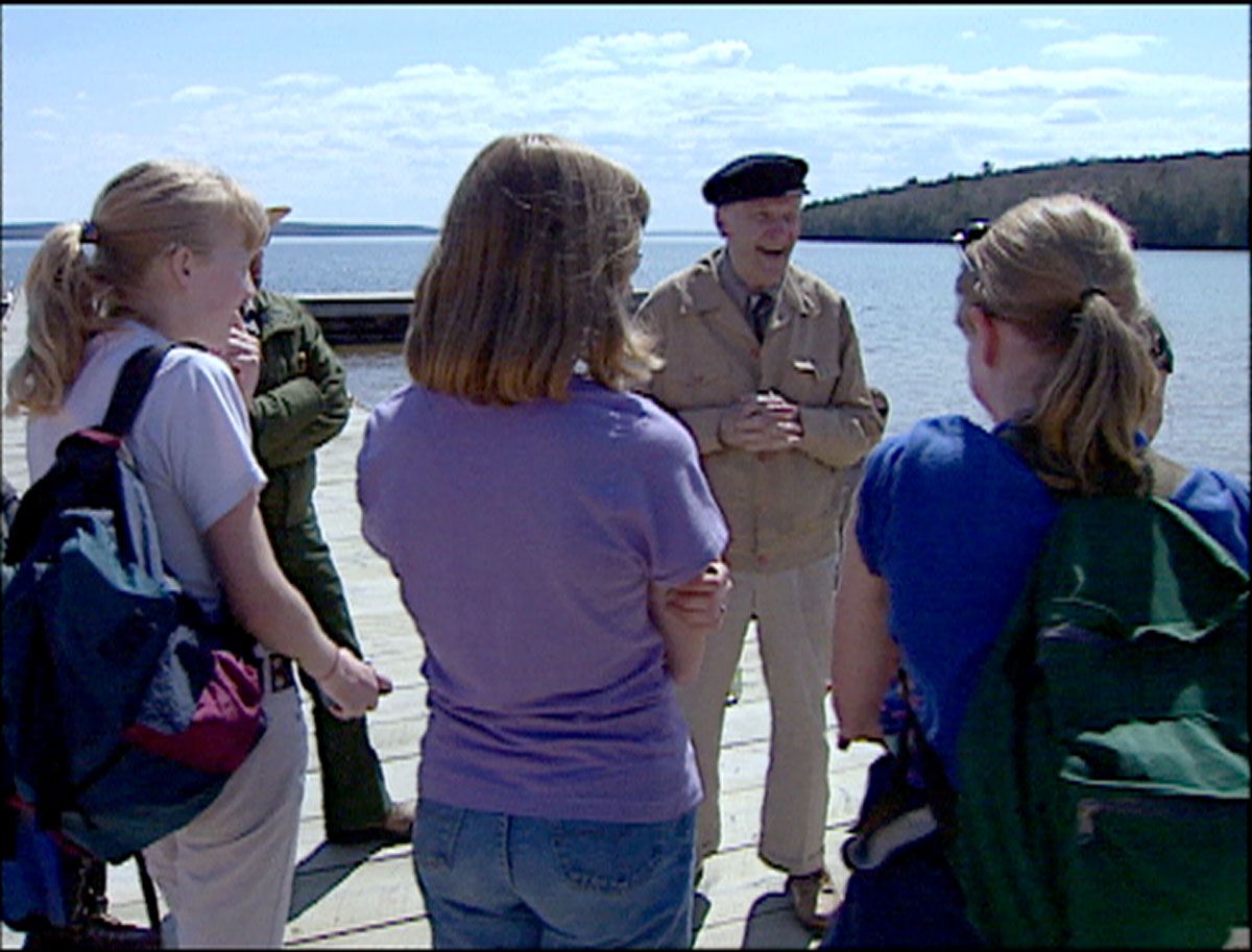 Gaylord Nelson visiting with a group of students during a visit to Quarry Bay on Stockton Island