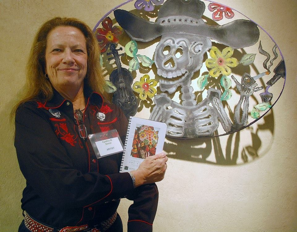 Cynthia Daniel with Her Art and a Datebook at Day of the Dead Exhbition