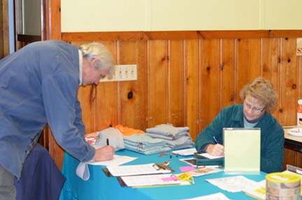 A man signing up at an information table