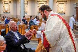 Archbishop Alfred Hughes and Deacon Joe Fessenden distribute communion to his family. Joe was ordained early because of his father's illness. Bishop David Choby ordained Dan Steiner and Joe Fessenden to the transitional diaconate during a Mass at the Cathedral of the Incarnation.