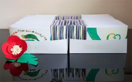 Abi & Rob Little Bespoke Book Wedding Invitations stacked in boxes.