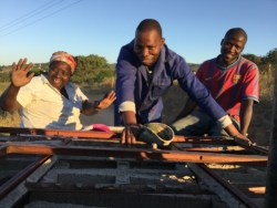 Make and other community members in bed of pickup truck after successfully going around to collect donated building material for making the house