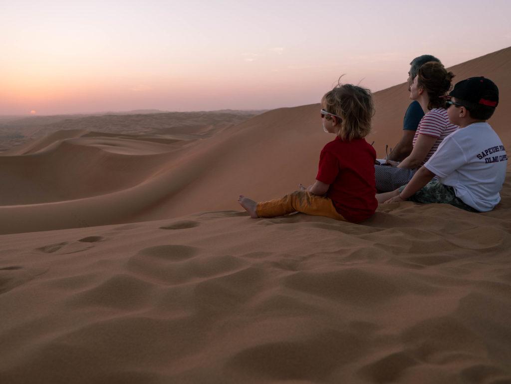 famille regardant le coucher d e soleil en haut des dunes