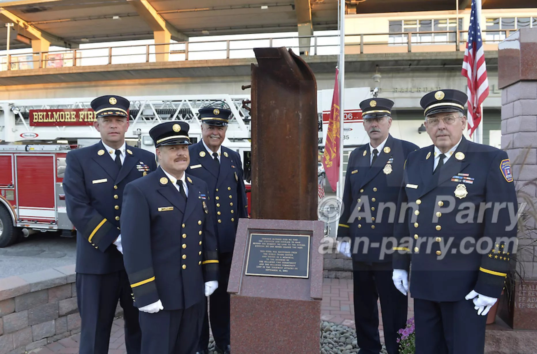 Bellmore, NY, USA. 11th Sept. 2015. L-R, Bellmore Fire Dept. Chief DANIEL HOLL, Pastor and Chaplain JAMES BARNUM, 1st Deputy VINCENT MONTERA, 2nd Deputy TOM STOERGEN, and Chaplain DENNIS RICH stand next to a monument that's a piece of structural steel from the Twin Towers, during the Bellmore Memorial Ceremony for 3 Bellmore volunteer firefighters and 7 residents who died due to 9/11 NYC terrorist attacks. Elevated platform of Bellmore LIRR Station is in background.