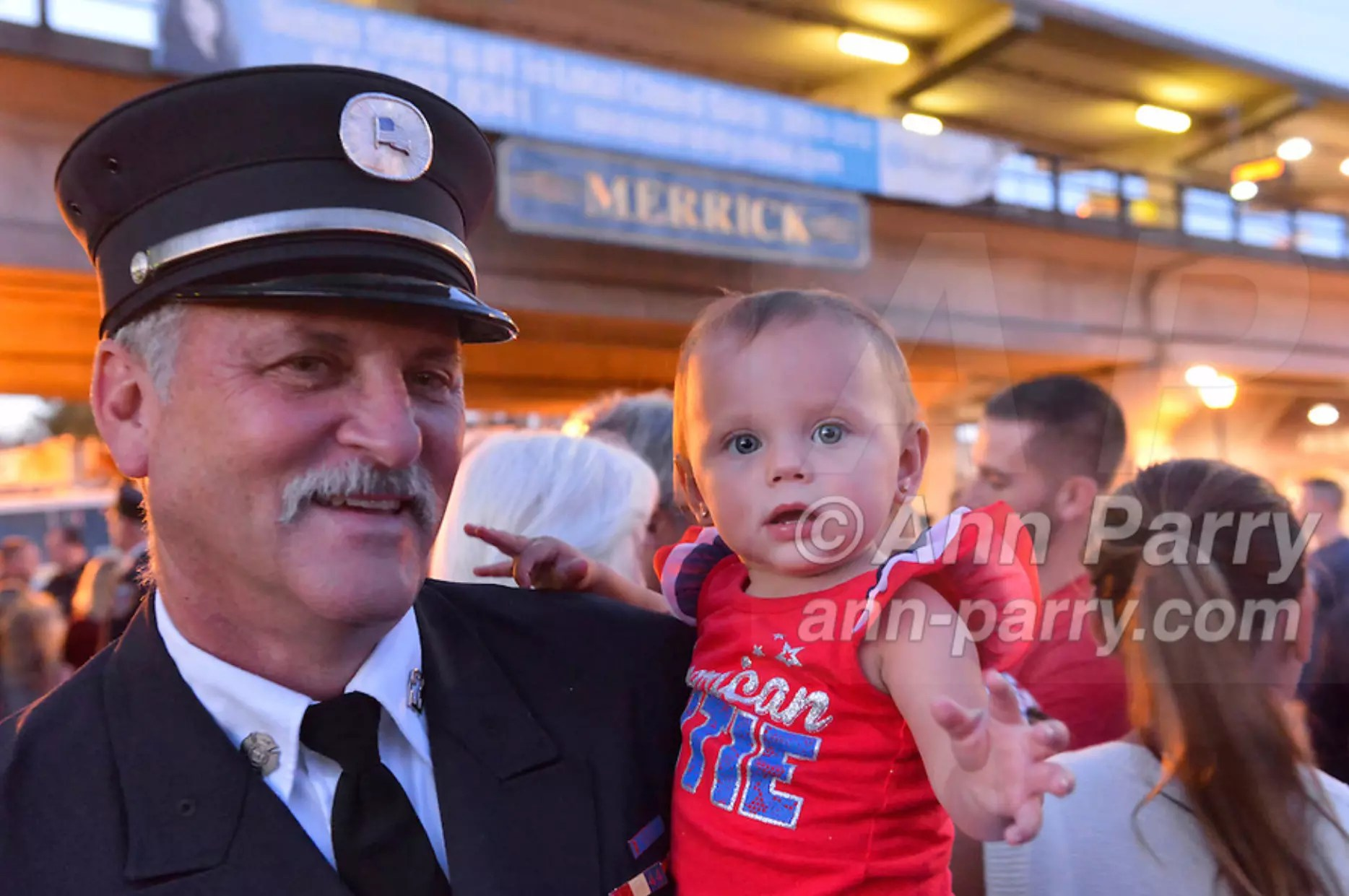 Merrick, NY, USA. Sept. 11, 2015. RILEY E. GIES, one-year-old granddaughter of Fire Chief Ronnie E Gies who died responding to 9/11 NYC Terrorist Attack, is held by CRAIG MALTZ, a Bellmore volunteer firefighter, at Merrick Memorial Ceremony for Merrick volunteer firefighters and residents who died due to 9/11 terrorist attack at NYC Twin Towers. Ex-Chief Ronnie E. Gies of Merrick F.D. and FDNY Squad 288, and Ex-Captain Brian E. Sweeney, of Merrick F.D. and FDNY Rescue 1, died responding to the attacks on September 11, 2001.