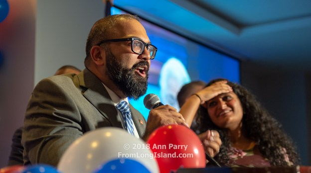 Garden City, New York, USA. November 6, 2018. Nassau County Democrats watch Election Day results at Garden City Hotel, Long Island. KEVIN THOMAS was elected New York State Senator for 6th District. His wife RINCY is on stage with him.
