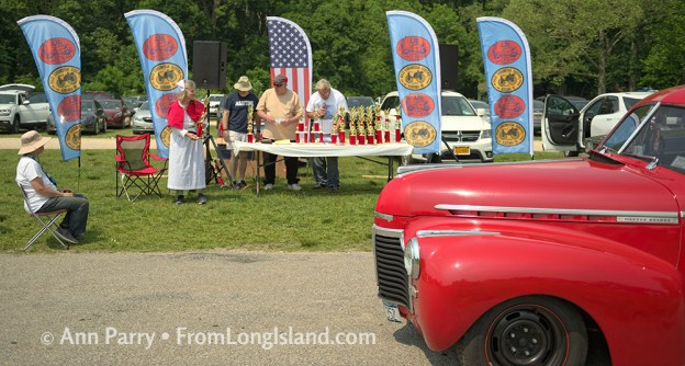 Old Westbury, New York, USA. June 2, 2019. A red Chevrolet Master Deluxe antique car drives by the trophy table, and ALTHEA TRAVIS, standing at left, dressed in vintage-style white and red nurse's costume, hands out trophies at the 53rd Annual Spring Meet Antique Car Show, sponsored by the Greater NY Region (NYGR) of the Antique Car Club of America (AACA), at Old Westbury Gardens . © 2019 Ann Parry, FromLongIsland.com