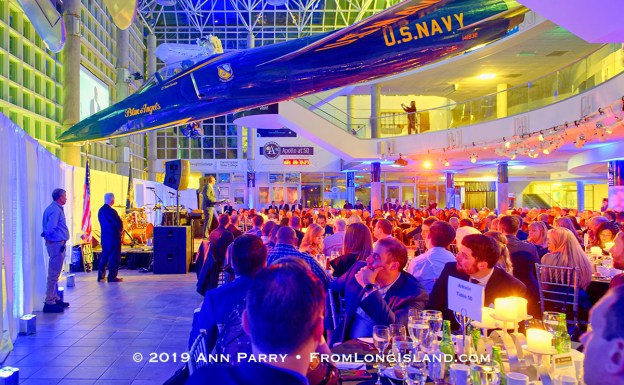 Garden City, NY, U.S., Nov. 14, 2019. HUNTLEY LAWRENCE, the Aviation Leadership Award honoree, speaks at podium under U.S. Navy Grumman F11 jet suspended from atrium ceiling, as guests look on during 7th Annual Cradle of Aviation Museum Air and Space Gala.