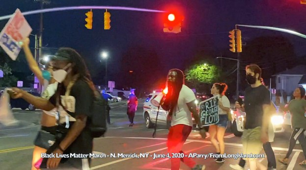 North Merrick, New York, U.S. June 4, 2020. Black Lives Matter March heads east on Jerusalem Ave and then turns north onto Bellmore Avenue, toward eastbound entrance to Southern State Parkway. Shortly before protestors arrive, Nassau County Police officers park several patrol cars at intersection to stop and divert traffic to make path for peaceful march of largely of young marchers, black and white . Many marchers wore face masks, some masks covering mouth and nose, some masks lowered below mouth as they chanted. Young black man with megaphone led the chant: megaphone man: NO JUSTICE marchers: NO PEACE megaphone man: NO RACIST marchers: POLICE Signs marchers carried included: RIP GEORGE FLOYD - IGNORANCE IS ALWAYS AFRAID OF CHANGE - BLM! - BLACK LIVES MATTER - NO RACIST POLICE