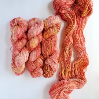 left to right, 3 skeins of coral yarn and an opened up skein last. 'Living Coral' colorway