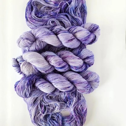 top to bottom, 3 skeins of yarn in 'Geode' colorway, with a opened up skein under them