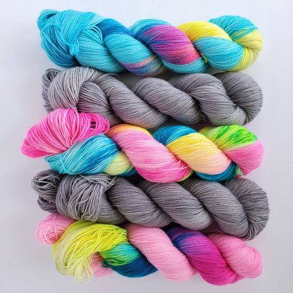 5 skeins of yarn laid top to bottom, 'Blue Lagoon', 'Sour Candy' and '90s kid' are alternated by 'Stone' colorway