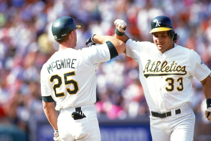 OAKLAND, CA - 1990: Jose Canseco #33 and Mark McGwire #25 of the Oakland Athletics celebrate during a 1990 MLB season game at Oakland-Alameda County Coliseum in Oakland, California. (Photo by Otto Greule Jr/Getty Images)