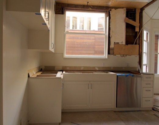 Kitchen Window View with Fridge, Above Window Light, Cabinet, Countertops and Dividing Wall Removed, Day Two