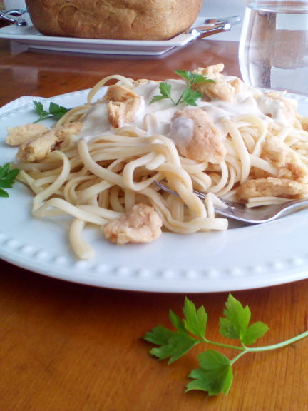 "Vegan ""Chicken"" Alfredo on a white plate with parsley garnish in front, and bread in the background"
