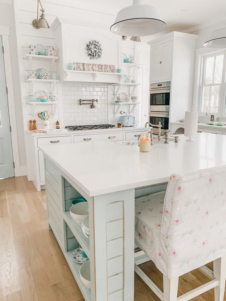 Blue kitchen island with white bar stools