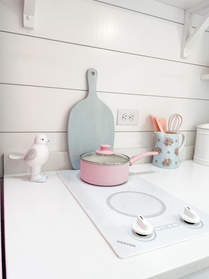 cooktop with pink pan and blue cutting board