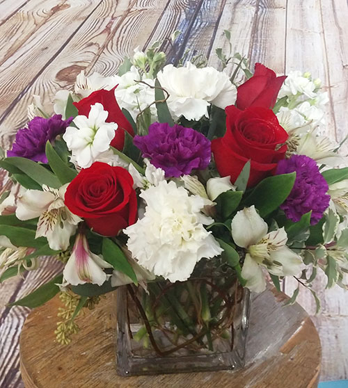 Abounding Love arrangement with roses, carnations, alstromeria, and stock flowers