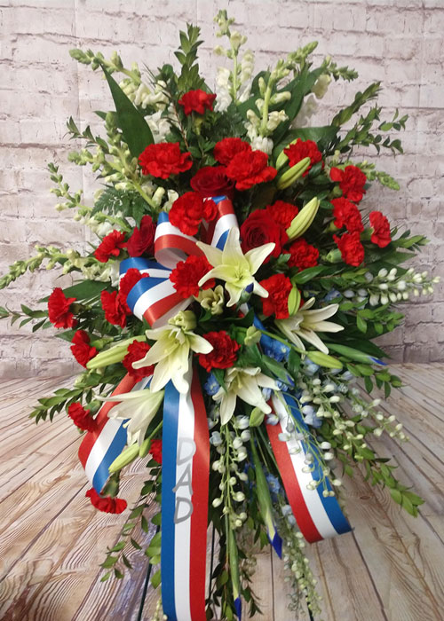 standing spray of red carnations, white lilies, snaps and delphinium