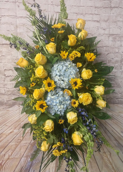 standing spray of yellow roses, blue delphinium, sunflowers an hydrangeas