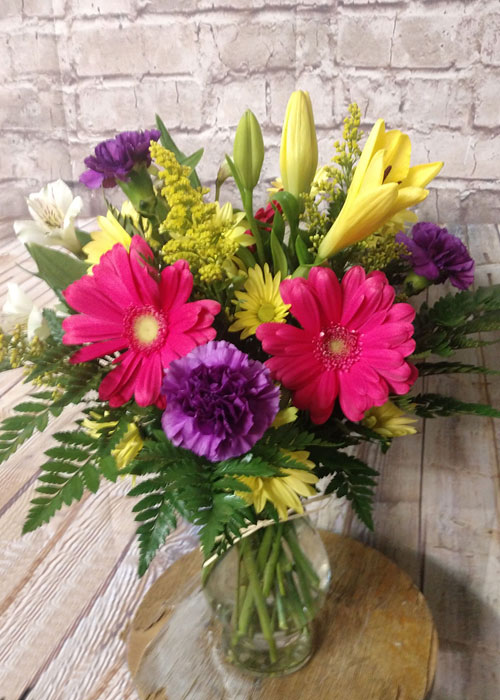 Yellow lilies, pink gerbers, purple carnations, daises, alstromeria and fillers